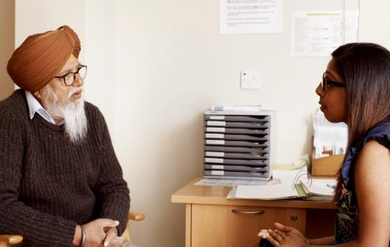 A person discussing their cancer diagnosis with their doctor in a consultation room