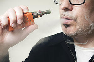 Photo of man using an e-cigarette