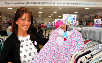 A Cancer Research UK shop manager holding up a piece of clothing