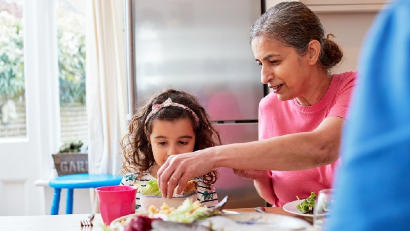 Grandmother giving salad to grandchild