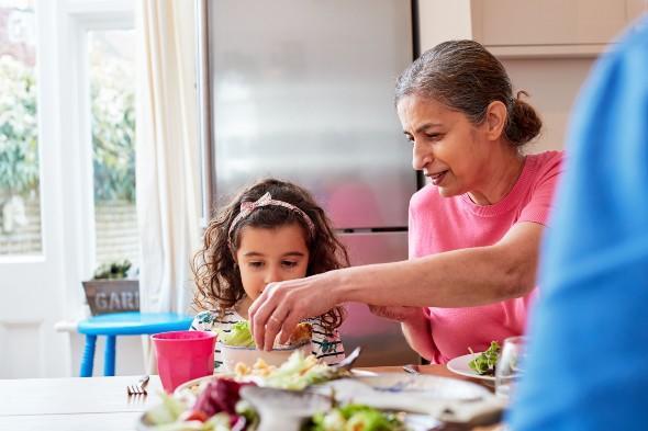 Grandmother giving salad to grandchild