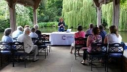 A legacy event - a member of CRUK staff talking to a room of people