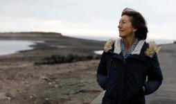 Linda, a CRUK pledger walking on the beach