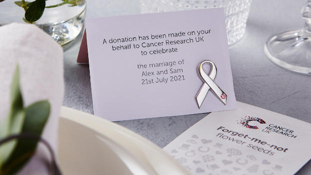 A Cancer Research UK ribbon pin badge with printed namecard, and forget-me-not seed wedding favours.