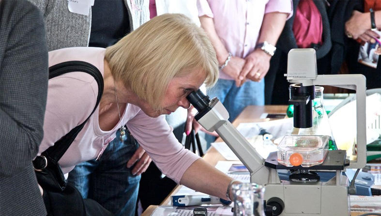 Supporter looking into microscope