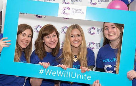 Four fundraisers hold up a photo border and smile under the hashtag '#We Will Unite'