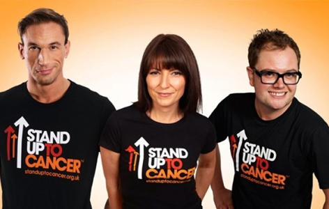 Dr Christian Jessen, Davina McCall and Alan Carr stand on an orange background wearing Stand Up To Cancer t-shirts
