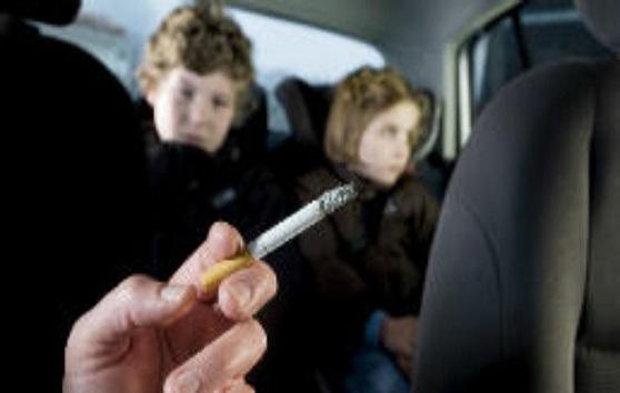 Children breathing in second-hand smoke in a car