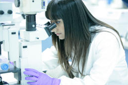 A Cancer Research UK scientist looks down her microscope