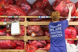 A stock processing volunteer with bags of donated items in a Cancer Research UK charity shop