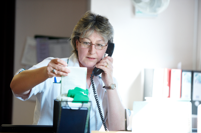 A cancer nurse looks at some results whilst on the telephone