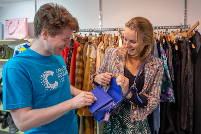 Male shop volunteer talking to a female customer holding a handbag in a charity shop