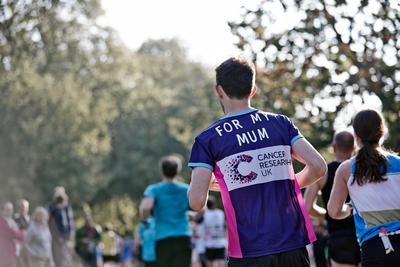 Male runner, wearing a CRUK runner vest, taking part in the Royal Parks Half Marathon