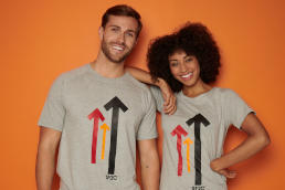 A man and a woman wearing grey Stand Up To Cancer t-shirts