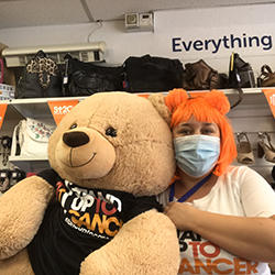 Image of girl in mask holding a teddy bear