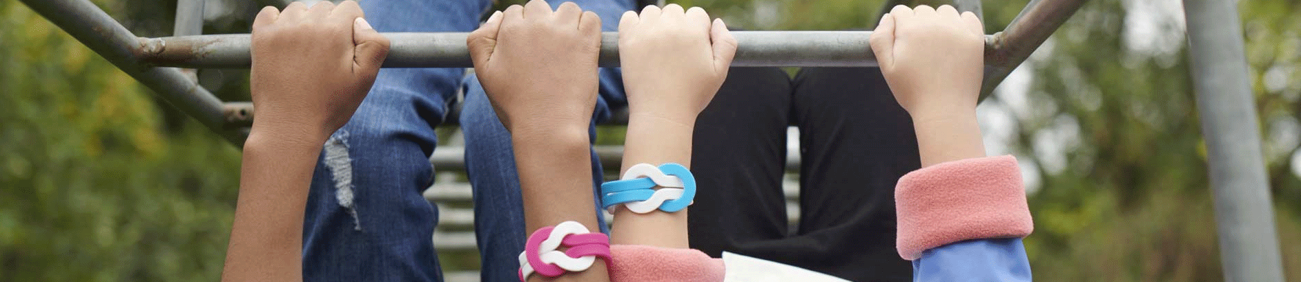 Children upside-down on climbing frame wearing pink and blue Unity Bands
