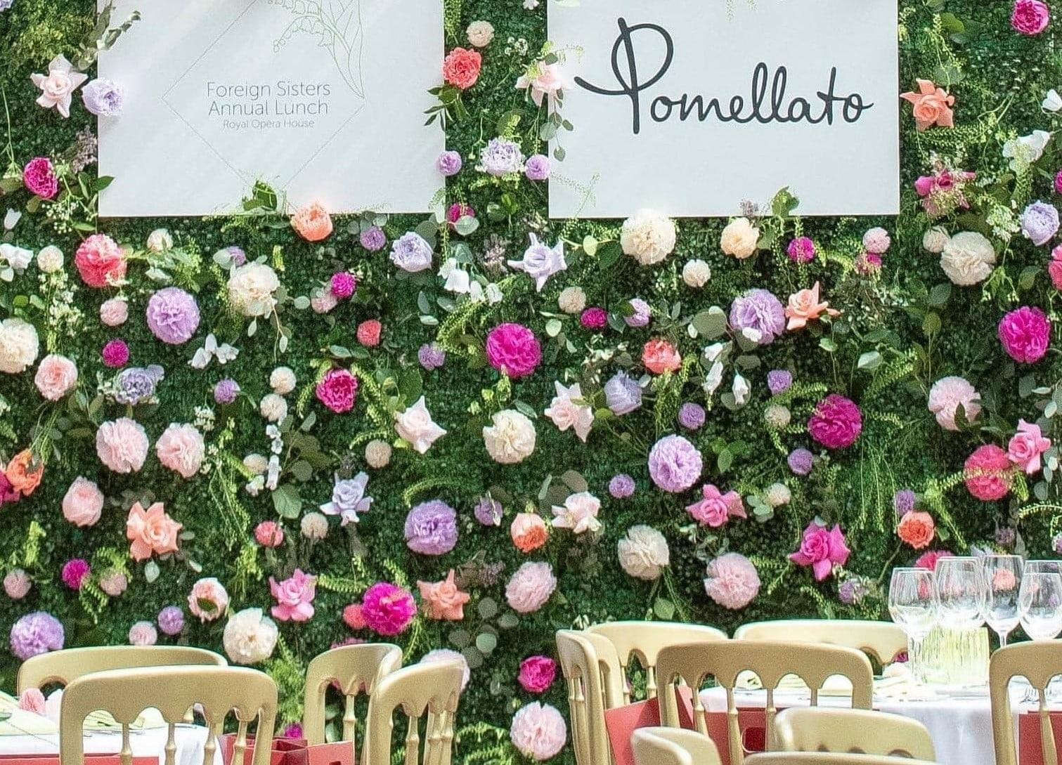 Wall of flowers with the Pomellato sign on it