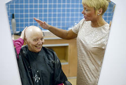 Woman smiling into the mirror as she strokes and admires her newly shaven head