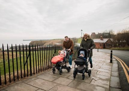 Two fathers walking with their children in prams