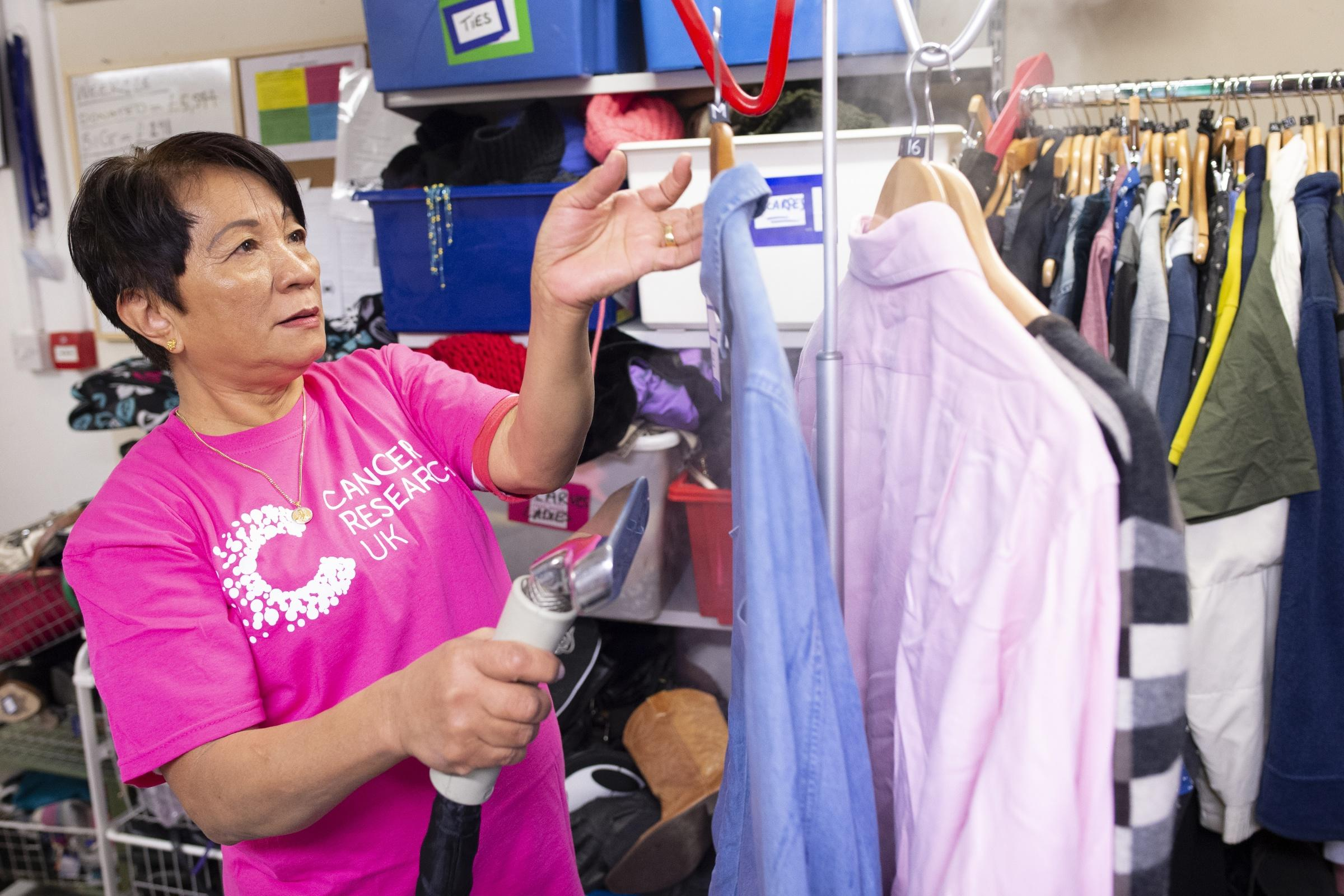 A female volunteer is steaming clothes in one of our shops, she is wearing a branded t shirt and looks happy.
