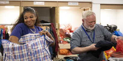 Two shop volunteers unpacking bags of clothes donations