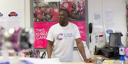 A volunteer standing at the till in a CRUK shop