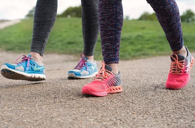 An image of two women walking wearing trainers