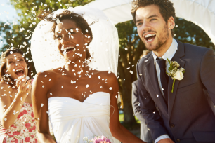 Couple smiling with confetti over them.