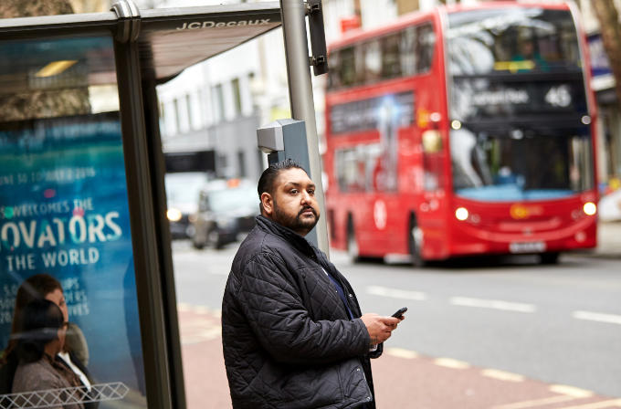 Photo of a man at a bus stop in London