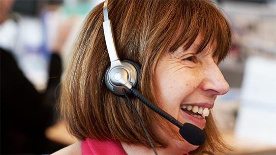 A cancer nurse talking on the phone, wearing a headset