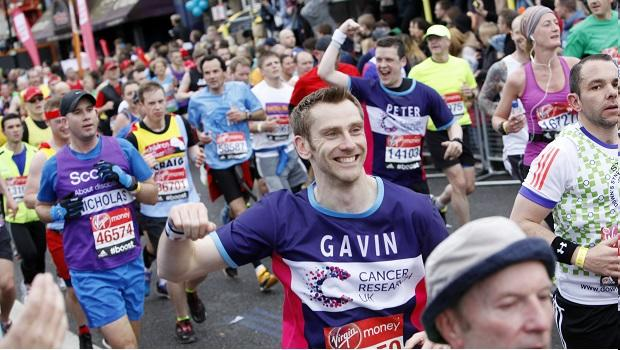 Runner taking on an event for CRUK with their fist raised in the air in celebration.