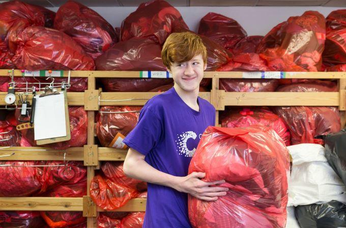 Volunteer assisting in our hub, carrying an orange sack of donated items