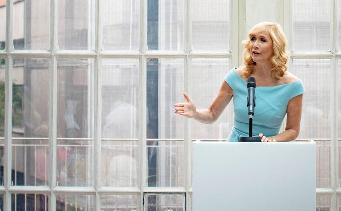 Tania Bryer speaking at an event in front of a large window
