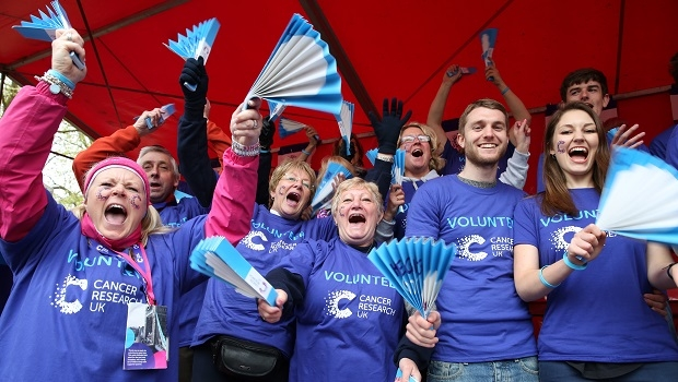 Cancer Research UK Cheer Team waving banner and cheering at London Marathon.