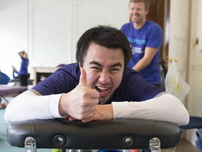Massage therapist treating a CRUK race participant who is giving thumbs up on the massage bed