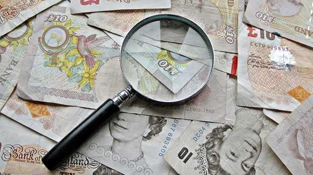 Magnifying glass sitting on pound notes.