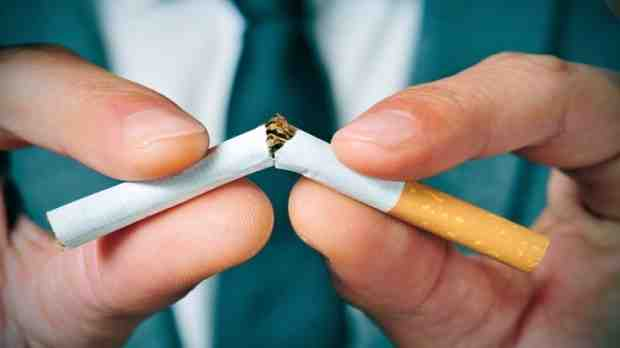 Man breaking cigarette in half to quit smoking