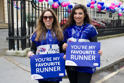 Two female race marshals with 'you're my favourite runner' signs