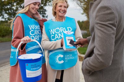 Two female volunteers with collection buckets, wearing blue World Cancer Day tabards, fundraising for World Cancer Day