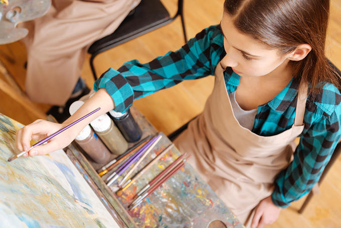 A photo taken from above with a girl painting onto an easel