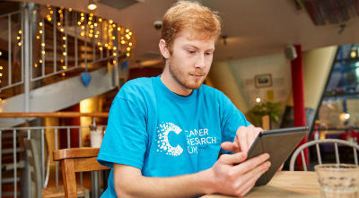 Male e-campaigner wearing CRUK tshirt, sitting in a cafe, using his tablet to e-campaign.
