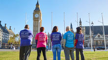 Cancer Research UK supporters standing in front of Parliament wearing shirts that say 'Together we are fighting cancer'