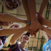 Cancer research basketball performing a team huddle