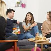 Three women and one man sit on a sofa around a coffee table with coffee cake and scones. Fundraising leaflets sit on the table. They are mid-conversation and smiling.