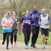 Three women and two men wearing Cancer Research UK branded clothing run in a group along a path in a green park with trees. They are smiling.