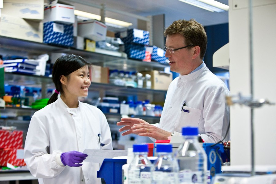Two CRUK scientists talking in a lab