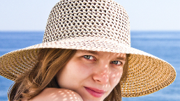 Woman wears a straw hat in the sun